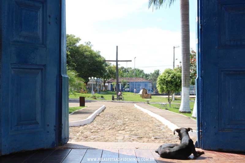 Cocais - MG - Cachorro na porta da Igreja Matriz de Nossa Senhora do Rosário observa a Praça
